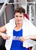 Handsome man sitting on a bench press after exercises — Stock Photo