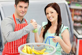 Salesman in a grocery store giving apples to his smiling female — Stock Photo