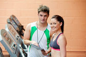 Pretty woman on a treadmill with her coach showing results — Stock Photo