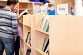 Close-up of a bookshelves in a library with students reading boo — Stock Photo