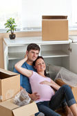 Adorable couple sitting on the floor in their new house during r — Stock Photo