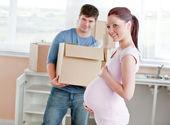 在 backgro 中的丈夫微笑未来的母亲在新的厨房 — 图库照片