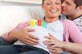 Ung man kysser sin gravida hustru med baby bokstäver på bel — Stockfoto