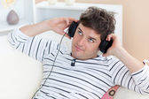 Thoughful man listening music looking the top sitting in the sof — Stock Photo