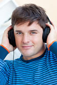Peaceful man listening music using headphones smiling at the cam — Stock Photo
