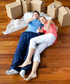 Happy couple lying on the floor in their new house doing thumbs- — Stock Photo