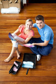 Beautiful couple sits on the floor picking colors — Foto Stock