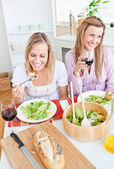 Two delighted female friends eating salad in the kitchen — Stock Photo
