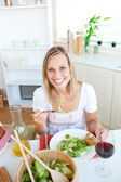 Smiling woman eating salad in the kitchen — Stock Photo