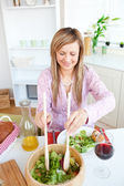 Radiant woman eating salad in the kitchen — Stock Photo