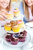 Close-up of two female friends eating pastries in the kitchen — Stock Photo