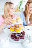 Portrait of two smiling female friends eating pastries in the ki — Stock Photo