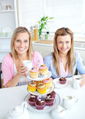 Portrait of two female friends eating pastries and drinking coff — Stock Photo