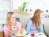 Two laughing female friends eating pastries and drinking coffee — Stock Photo