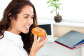 Hispanic businesswoman eating a doughnut in her office — Stock Photo