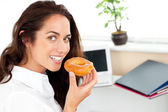Happy hispanic businesswoman eating a doughnut — Stock Photo