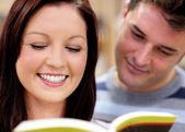 Close-up of a smiling couple of students reading a book — Stock Photo