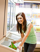 Smiling young woman holding a deep-frozen product — Stock Photo