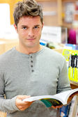 Serious young man reading a book — Stock Photo