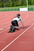 Athletic man waiting in starting block — Stock Photo