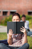 Concentrated female student reading a book sitting on grass — Stock Photo