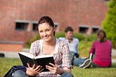 Delighted female student reading a book sitting on grass — Stock Photo