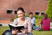 Aluna encantada lendo um livro sentado na grama — Foto Stock