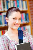 Joyful young caucasian woman holding a book — Stock Photo