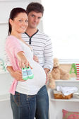 Cheerful pregnant woman holding baby shoes while husband touchin — Stock Photo