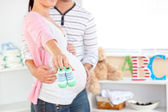 Close-up of a bright pregnant woman holding baby shoes while hus — Stock Photo