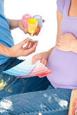 Close-up of a pregnant woman and her husband choosing colors — Stok fotoğraf