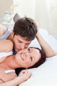 Affectionate caucasian couple lying on bed in the bedroom — Stock Photo