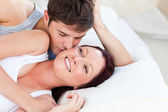 Caring caucasian couple lying on bed in the bedroom — Stock Photo