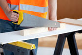 Close-up of a male worker sawing a wooden board — Foto Stock