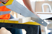 Close-up of a serious male worker sawing a wooden board — Stock Photo