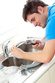 Caucasian man repairing a kitchen sink at home — Zdjęcie stockowe