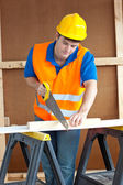 Handsome male worker wearing a yellow hardhat sawing a wooden bo — Stock Photo