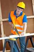 Charismatic male worker wearing a yellow hardhat sawing a wooden — Stock Photo