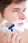 Bright caucasian man shaving in the bathroom — Stock Photo