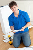 Charismatic young man reading the instructions to assemble furni — Stock Photo