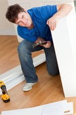 Smiling man assembling furniture and holding a hammer — Stock Photo