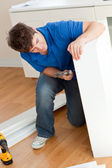 Good-looking man assembling furniture and holding a hammer — Stock Photo