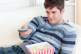 Bright young man eating popcorn and holding a remote lying on th — Stock Photo