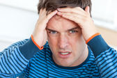 Caucasian man having a headache in the living-room — Stock Photo