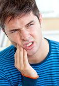 Homem caucasiano infeliz tendo uma dor de dente na sala de estar — Foto Stock