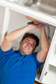 Charismatic man repairing his sink in the kitchen — Stock Photo