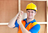 Assertive young male worker with a yellow helmet carrying a wood — Stock Photo