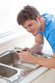 Assertive man repairing his sink in the kitchen — Stock Photo