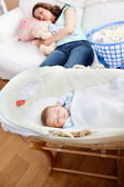Young mother sleeping on the sofa while her baby is sleeping in — Stock Photo
