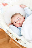 Portrait of a bright baby lying in his cradle — Stock Photo